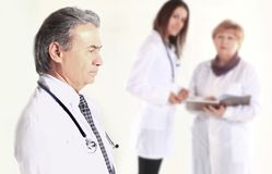 Portrait of an experienced doctor in the background of the employees of the medical center stock image