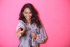 Expressive casual woman giving thumbs up. Portrait of expressive casual woman giving thumbs up on pink background Royalty Free Stock Photos