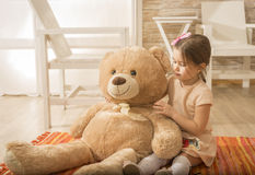 Portrait of expressive charming little girl hugging huge plush bear Royalty Free Stock Images