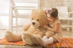 Portrait of expressive charming little girl hugging huge plush bear, laughing. Stock Photos