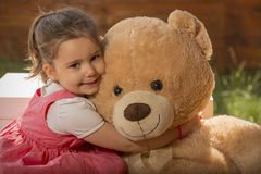 Portrait of expressive little girl hugging her toy bear Royalty Free Stock Photos