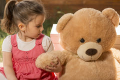 Portrait of expressive little girl hugging her toy bear Stock Photography