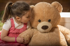 Portrait of expressive little girl hugging her toy bear Stock Images