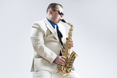 Portrait of Expressive Stylish Caucasian Saxophone Player Performing in White Suit Royalty Free Stock Image