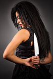 Portrait of an expressive young woman holding a big knife to her Stock Photo
