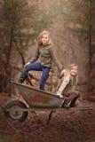 Portrait extérieur artistique de deux filles blondes jouant avec une brouette de roue dans des bois Images stock