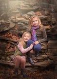 Portrait extérieur artistique de deux filles blondes s'asseyant sur des roches Image stock