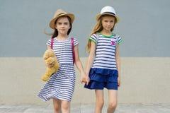 Portrait extérieur d'été de deux amie heureux 7, 8 ans tenant des mains Filles dans des robes rayées, chapeaux avec le sac à dos, Photographie stock libre de droits