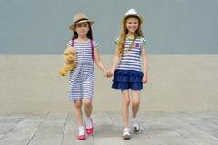 Portrait extérieur d'été de deux amie heureux 7, 8 ans tenant des mains Filles dans des robes rayées, chapeaux avec le sac à dos, Image libre de droits