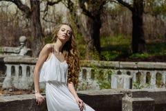 Portrait extérieur d'été de fille assez mignonne de jeunes Belle femme posant au vieux pont dans les dess blancs tenant le railin Photographie stock