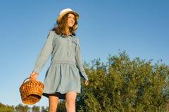 Portrait extérieur d'été de fille de l'adolescence avec des fraises de panier, chapeau de paille Fond de nature, paysage rural, p image libre de droits