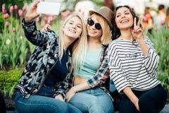 Portrait extérieur d'été de trois filles d'amusement d'amis prenant des photos avec le smartphone Photographie stock libre de droits