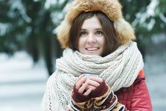 Portrait extérieur d'hiver de la jeune dame gaie tenant la tasse de touristes de flacon de vide avec la boisson chaude photographie stock