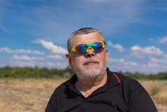 Portrait extérieur d'un aîné barbu dans des lunettes de soleil contre le ciel nuageux bleu image libre de droits