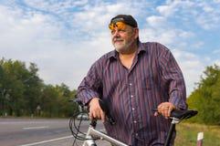 Portrait extérieur d'un homme supérieur barbu avec la bicyclette Photo stock