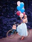 Portrait extérieur d'une belle fille blonde tenant des ballons et montant un vélo photos stock
