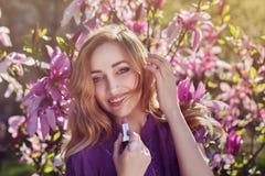 Portrait extérieur d'une jeune belle dame de sourire heureuse à l'aide du rouge à lèvres près de l'arbre de magnolia avec des fle Image libre de droits