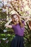 Portrait extérieur d'une jeune belle dame de sourire heureuse posant près de l'arbre de magnolia avec des fleurs Looking modèle à Image stock