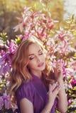 Portrait extérieur d'une jeune belle dame employant le parfum près de l'arbre de magnolia avec des fleurs Le modèle a fermé ses y Photo stock