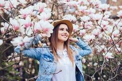 Portrait extérieur d'une jeune belle femme avec le chapeau d'été près de l'arbre de magnolia avec des fleurs photo libre de droits