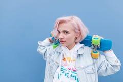 Portrait extérieur d'une jeune jolie fille avec la planche à roulettes sur un fond bleu image stock