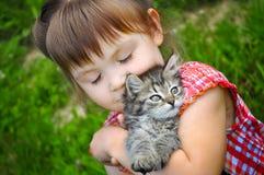 Portrait extérieur d'une petite fille mignonne avec le petit chaton, fille jouant avec le chat sur le fond naturel Images libres de droits