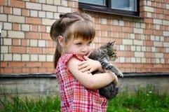 Portrait extérieur d'une petite fille mignonne avec le petit chaton, fille jouant avec le chat sur le fond naturel Photographie stock