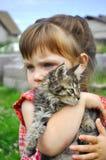 Portrait extérieur d'une petite fille mignonne avec le petit chaton, fille jouant avec le chat sur le fond naturel Image libre de droits