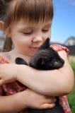 Portrait extérieur d'une petite fille mignonne avec le petit chaton, fille jouant avec le chat sur le fond naturel Photos stock