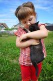 Portrait extérieur d'une petite fille mignonne avec le petit chaton, fille jouant avec le chat sur le fond naturel Photos libres de droits