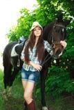 Portrait extérieur de belle cow-girl avec le cheval en vert Photo libre de droits