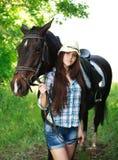 Portrait extérieur de belle cow-girl avec le cheval en vert Photos libres de droits