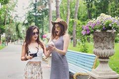 Portrait extérieur de deux amis observant des photos avec un smartphone Photos libres de droits