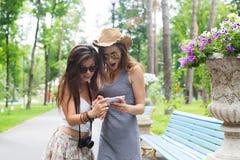 Portrait extérieur de deux amis prenant des photos avec un smartphone Image libre de droits