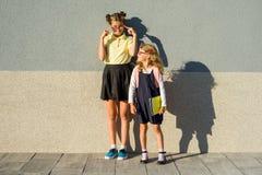 Portrait extérieur de deux filles Étudiant de lycée et un étudiant d'école primaire près du mur gris de l'école Images libres de droits