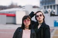 Portrait extérieur de deux jeunes belles filles dans les lunettes de soleil et l'habillement foncé sur le fond du paysage urbain Images libres de droits