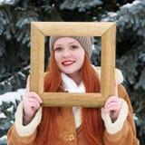 Portrait extérieur de femme dans le cadre en bois de photo à l'hiver Temps de Milou en parc d'arbre de sapin Photographie stock