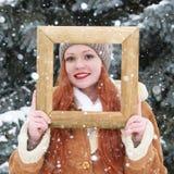 Portrait extérieur de femme dans le cadre en bois de photo à la saison d'hiver Temps de Milou en parc d'arbre de sapin Photographie stock