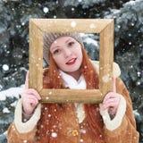 Portrait extérieur de femme dans le cadre en bois de photo à la saison d'hiver Temps de Milou en parc d'arbre de sapin Image stock