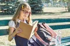 Portrait extérieur de jolie petite fille en verres d'uniforme scolaire, avec la bouteille de sac à dos de l'eau, livre de lecture photos libres de droits