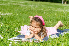 Portrait extérieur de la fille d'enfant en bas âge lisant un livre Photo libre de droits
