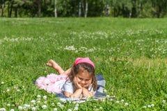 Portrait extérieur de la fille d'enfant en bas âge lisant un livre sur b naturel Photographie stock libre de droits