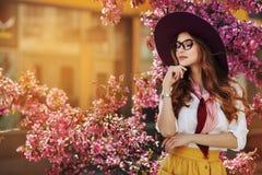 Portrait extérieur de la jeune belle dame à la mode posant près de l'arbre fleurissant Accessoires élégants de port modèles et Images stock