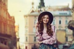 Portrait extérieur de la jeune belle dame de sourire à la mode posant sur la vieille rue Chapeau et vêtements élégants de port mo Photos libres de droits