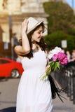 Portrait extérieur de la jeune belle dame de sourire heureuse marchant sur la rue Vêtements blancs élégants de port modèles Photo libre de droits