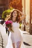 Portrait extérieur de la jeune belle dame de sourire heureuse marchant sur la vieille rue Vêtements blancs élégants de port modèl Photographie stock