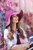 Portrait extérieur de la jeune belle dame de sourire heureuse posant près de l'arbre fleurissant Accessoires élégants de port mod Photos stock