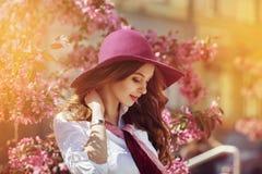 Portrait extérieur de la jeune belle dame de sourire heureuse posant près de l'arbre fleurissant Accessoires élégants de port mod Images stock