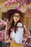 Portrait extérieur de la jeune belle dame de sourire heureuse posant près de l'arbre fleurissant Accessoires élégants de port mod Photos libres de droits