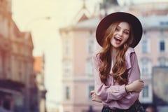 Portrait extérieur de la jeune belle dame heureuse à la mode posant sur la rue Chapeau à large bord élégant de port modèle Image stock